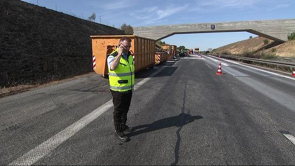 Polizist begutachtet eine Unfallstelle auf der Autobahn