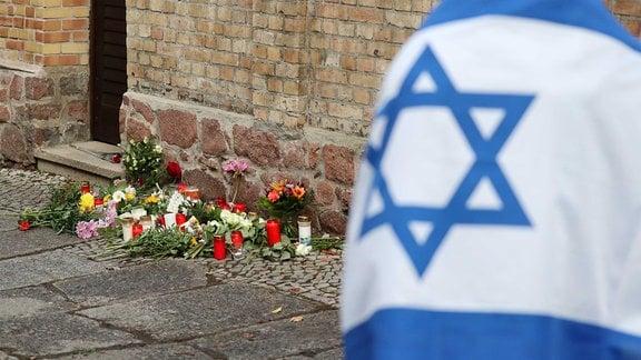 Ein Mann mit einer Israel-Flagge steht vor der Synagoge, wo Blumen und Kerzen stehen und liegen.