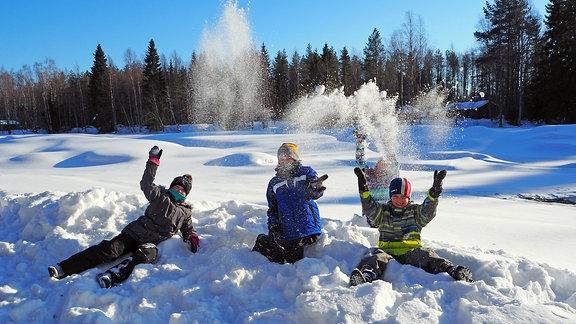 Drei Kinder spielen im Schnee