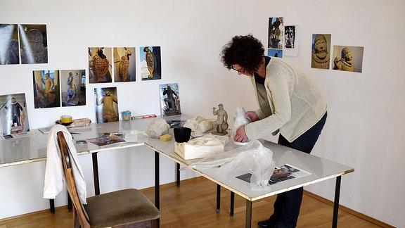 Frau hantiert mit kleinen Plastiken an einem Tisch.