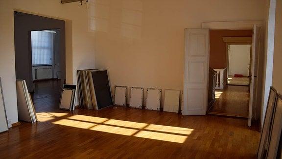 leerer Raum mit mehreren Bilderrahmen am Boden.