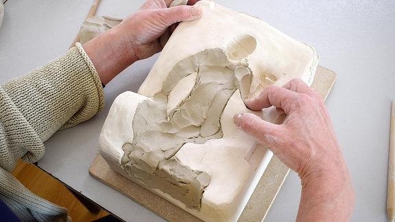 Eine Plastik wird in eine Form gepresst.