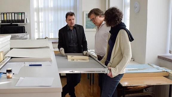 Zwei Männer und eine Frau schauen in altes Kartenmaterial im Museum.