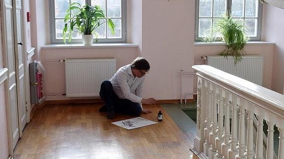 Ein Mann zeichnet etwas auf einem Treppenabsatz.