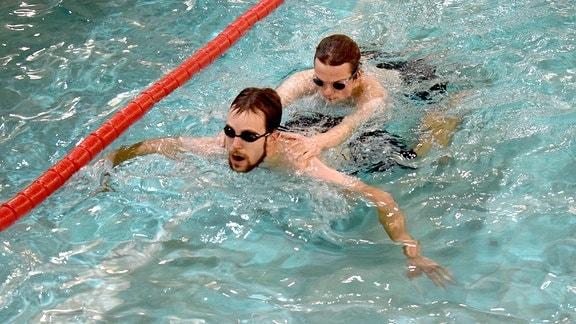 Zwei junge Männer schwimmen in einem Becken.