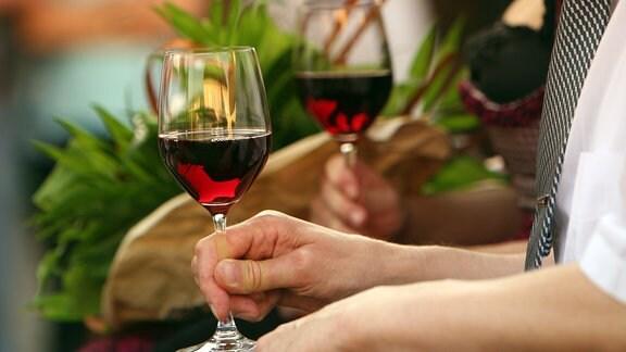 Hände halten Weingläser