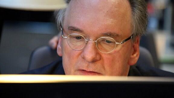 Eine Nahaufnahme von Ministerpräsident Reiner Haseloff, der am Computer sitzt.