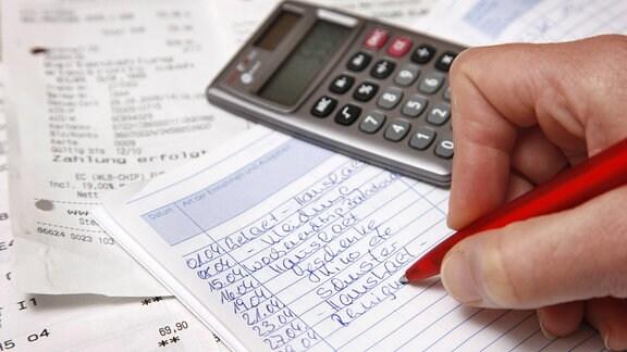 Mann notiert etwas in ein Haushaltsbuch