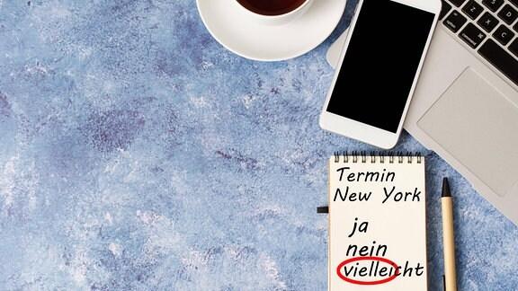 Smartphone, Laptop und Kaffetasse auf einem Schreibtisch