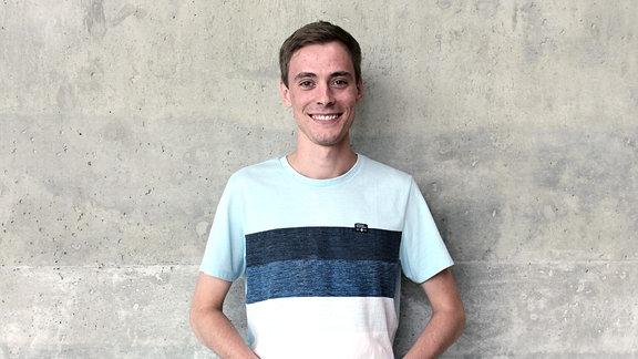 Ein junger Mann mit kurzem, dunkelblondem Haar steht lächelnd vor einer Betonwand.