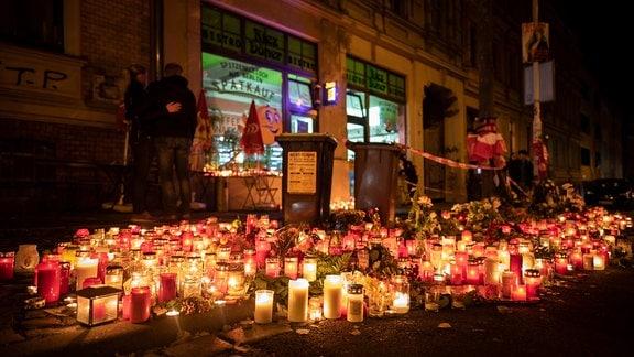 Kerzen und Grablichter brennen vor einem Döner-Imbiss