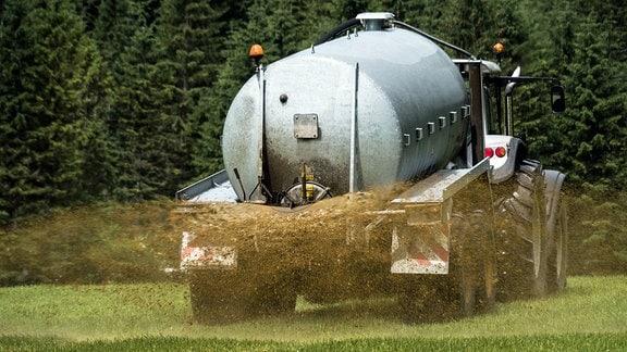 Ein Bauer bringt Gülle auf einem Feld aus.