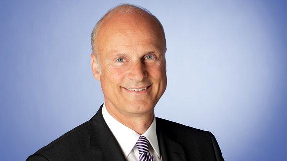 Carl-Ludwig Thiele, Vorstandsmitglied der Deutschen Bundesbank, vor einem blauen Hintergrund