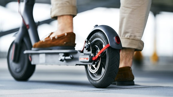Mann steht auf einem E-Scooter