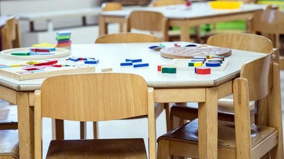 In einem leeren Kindergarten liegt Spielzeug auf einem Tisch.