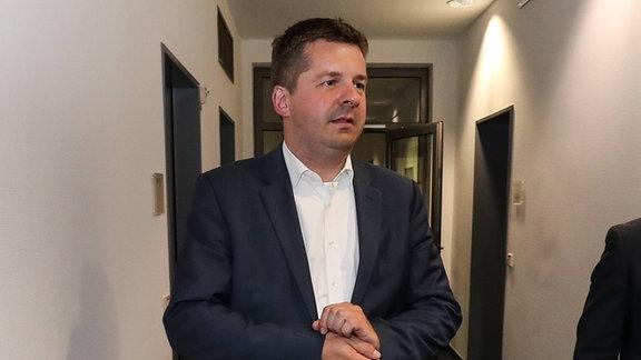 Sven Schulze, ein mittelalter Mann im Anzug steht in einem Bürogang und nestelt an seinen Handgelenken