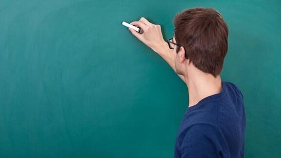 Lehrer steht an einer Tafel