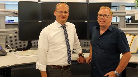 Thomas Zeug, Leiter der zentralen Leitstelle DB Regio Südost, und Matthias Mehl, Fachreferent Güterverkehr & Bereichsdisposition bei DB Netz stehen vor einem Arbeitsplatz mit mehreren Monitoren