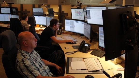 Mehrere Männer sitzen an abgerundeten Schreibtischen mit mehreren Bildschirmen