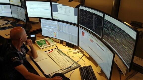 Blick von oben auf den Arbeitsplatz eines Verkehrsdisponenten mit vielen Bildschirmen