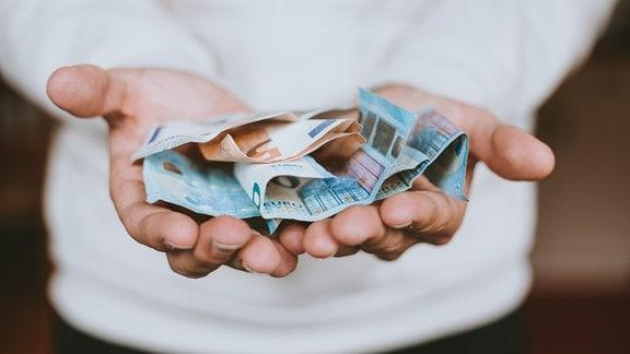 Zwei Hände halten mehrere Euro-Banknoten.