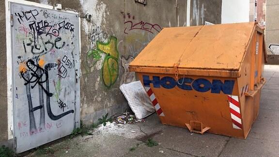 Eine Häuserwand ist mit Graffitis beschmiert, eine alte Matratze liegt hinter einem Behälter für Bauschutt