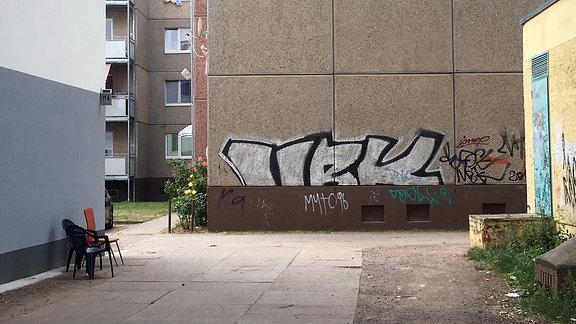 Eine Häuserwand ist mit Graffitis beschmiert, drei Plastikstühle stehen vor alten Wohnblocks