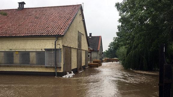 Straßen stehen unter Wasser. Sandsäcke sind vor Hauseingängen gestapelt