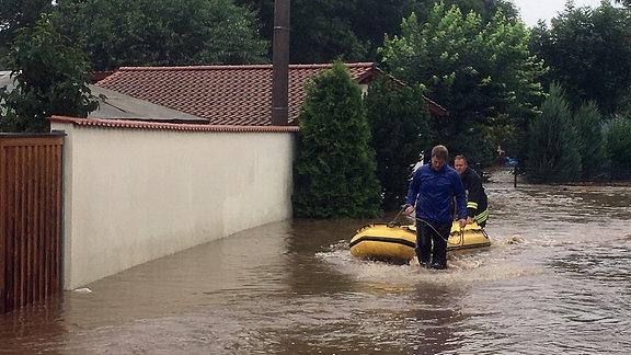 Zwei Männer waten durch Wassern und ziehen ein Schlauchboot hinter sich her
