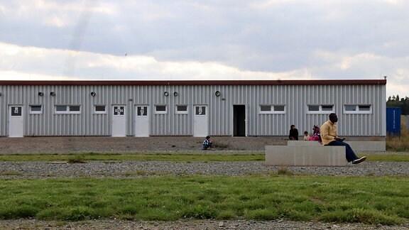 Geflüchtete sitzen im August 2017 auf einer Bank auf dem Gelände der Landes-Aufnahmeeinrichtung/Zentralen Anlaufstelle (ZASt) in Halberstadt