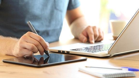 Junger Mann arbeitet auf einem Laptop.