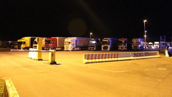 Ein Autobahn-Parkplatz voller Lkw bei Nacht
