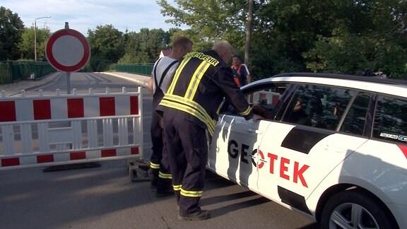 Zwei Feuerwehrmänner sprechen mit einem Autofahrer