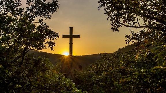 Sonnenuntergang hinter einem Hügel mit Kreuz