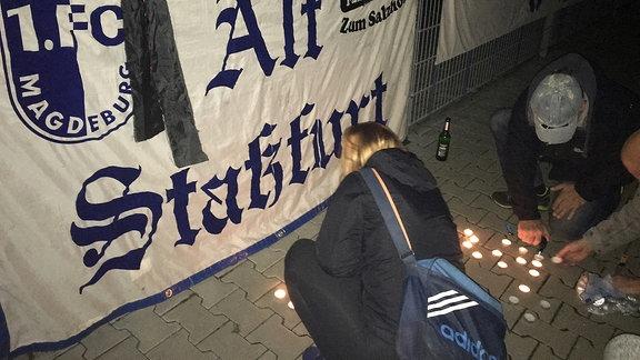 Eine Frau und ein Mann zünden Teelichter vor dem Stadion des 1. FC Magdeburg an