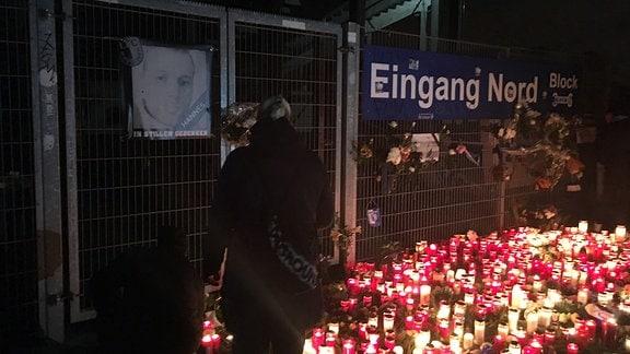 Zahlreiche Grabkerzen sind vor einem Eingang zum FCM-Stadion niedergelegt. Am Eingangstor hängt ein Schwarz-Weiß-Foto des verstorbenen Hannes