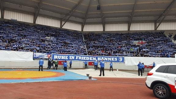 """Vor dem Auswärtsblock in Erfurt hängt ein banner mit der Aufschrift """"Ruhe in Frieden Hannes"""". Dahinter halten FCM-Fans ihre Fanschals in die Höhe"""