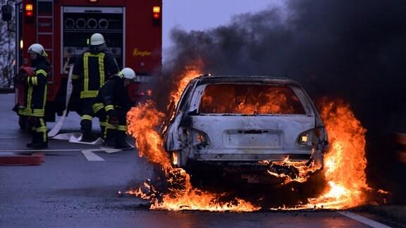 Ein Auto steht in Flammen. Im Hintergrund  befinden sich drei Feuerwehrmänner an einem Löschfahrzeug