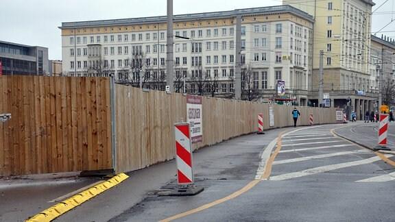 Straßenmarkierungen für Fußgänger entlang eines hölzernen Baustellenzauns
