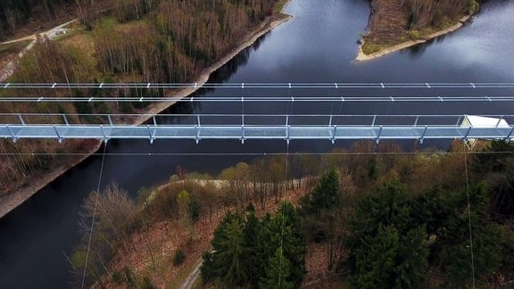 Luftbild der Fußgänger-Seilhängebrücke, die das Rappbodetal neben der gleichnamigen Talsperre überspannt