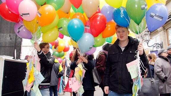 Drei Jugendliche halten Dutzende Luftballons in der Hand und lächeln in die Kamera