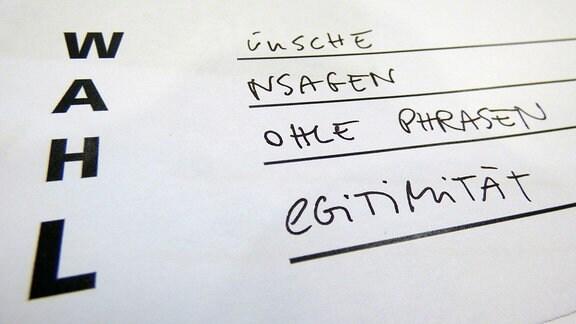 Die Befragten füllen die Umfragezettel aus, auf denen die Buchstaben W A H L jeweils mit Wörtern ergänzt werden sollen, die sie mit der Landtagswahl verbinden.