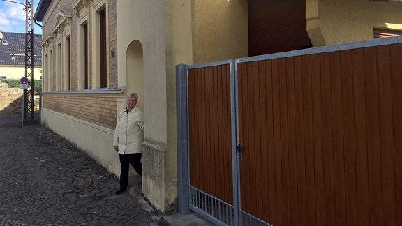 Eine Frau steht vor einem Haus an einer Straße