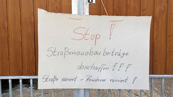 Stop – Straßenausbaubeiträge abschaffen! steht auf einem Schild, dass an einer Tür hängt
