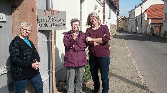 Drei Frauen stehen an einer Straße. An einem Haus ist ein Schild aufgestellt, dass den Stopp der Straßenausbaubeiträge fordert.