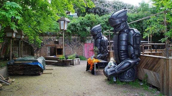 """Verlassene Holzgerüste, Statuen und Sitzgelegenheiten auf dem Außengelände des leeren Magdeburger Clubs """"Insel der Jugend"""""""