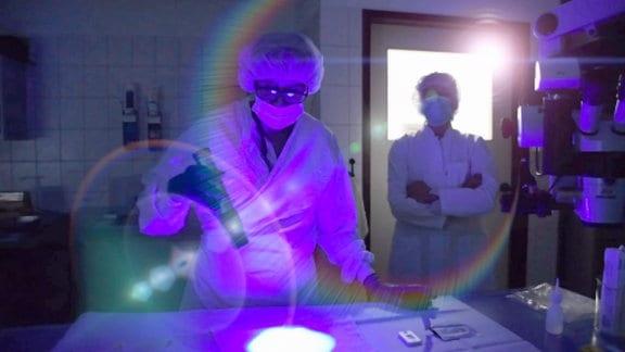 Zwei Forscher in weißen Kitteln in einem dunklen Labor