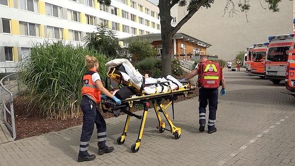 Zwei Sanitäter schieben eine Person auf einen Krankenbett Richtung Rettungswagen