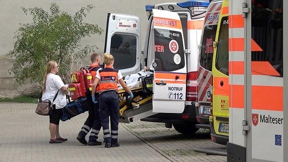 Zwei Sanitäter schieben eine Person auf einen Krankenbett in einen Rettungswagen