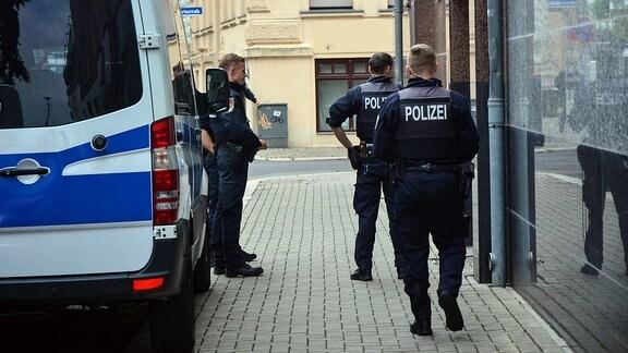 Mehrere Polizisten stehen vor einer Haustür